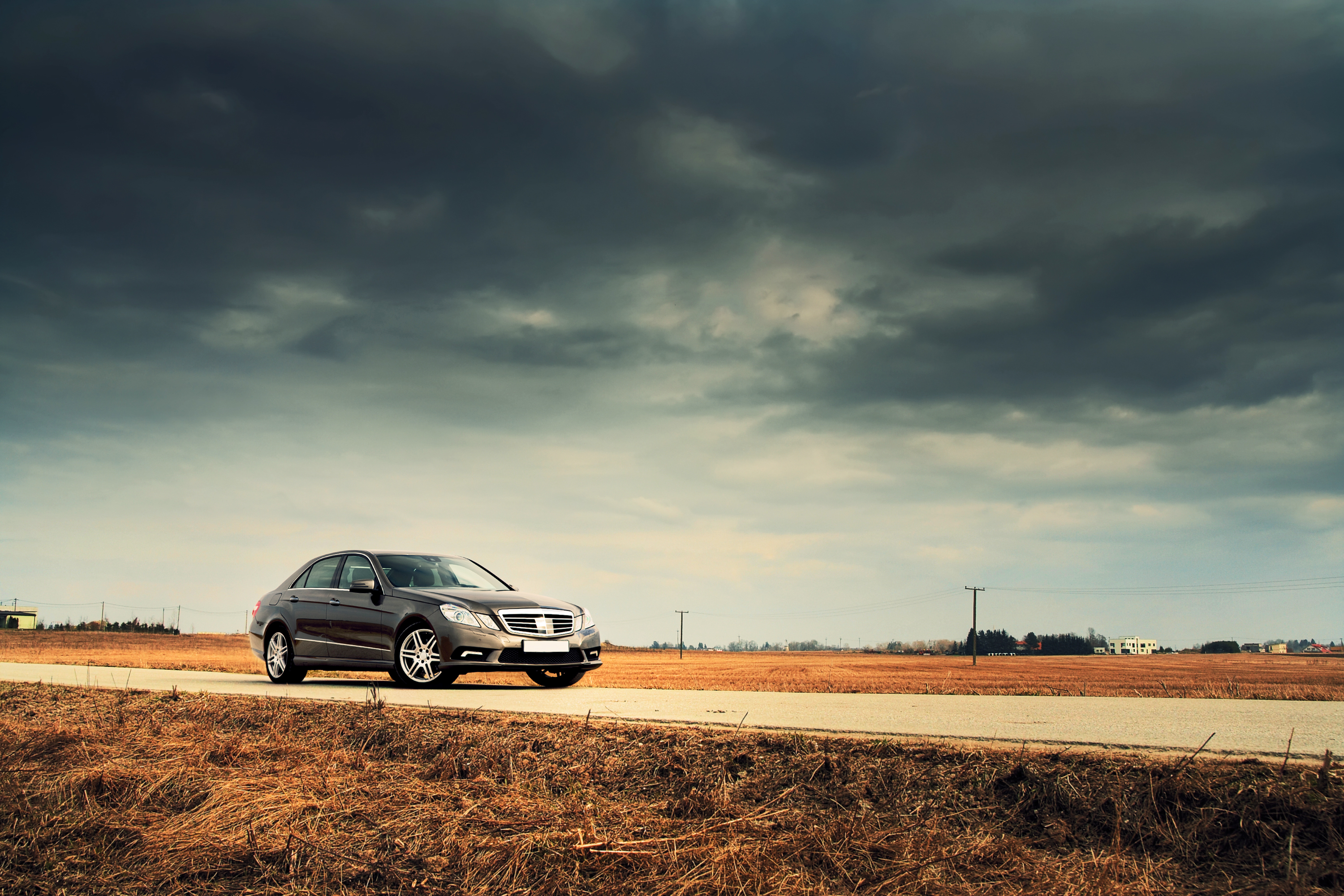Sedan-on-country-road-with-dramatic-sky